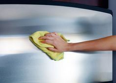 woman's hand with microfiber cloth polishing a stainless steel fridge door