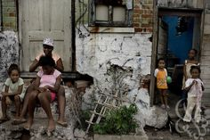 A Jamaican family sits out front of their tenement yard housing in the Matthews Lane area of Kingston June 16, 2008.  A recent United Nation...