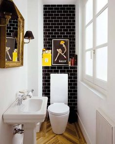 Love the black tile, with the wood floor. Gold mirror frame and sconces are different and good too! (via Nuevo Estilo)