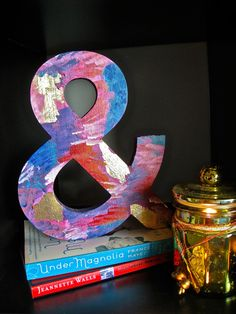 Gold Foiled Ampersand Home Decor. For those who share in my love of typography and gold. A wooden ampersand painted with acrylic paint. Features gold foil accents. Can be used to add a unique touch to a bookshelf or any other part of the home. Could also be added to a gallery wall (picture hanger would need to be added to back).Email me at editedwithart@gmail.com with a request or to receive pricing info. Etsy shop coming soon!