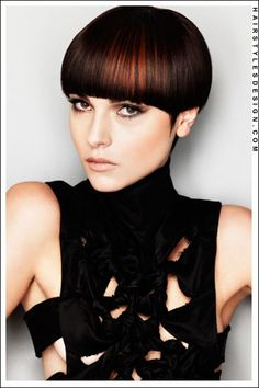 Hair Style: This is a cute hairstyle as the hair is short all around. Some may call this the bowl haircut as it has been rounded. Starting from the front, thick bangs are styled across. At the sides, the hair is styled to come to a point in front of the ears. At the sides, the hair partly covers the ears with the hair at back, short.  Hair Cut: The hair is short.  Hair Colour: A rich, warm espresso brown with copper shimmer highlights.