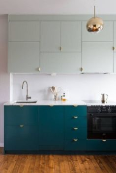 Two-tone cabinets with chic brass hardware help reinvent this streamlined IKEA kitchen into a color blocked showstopper. Two-tone cabinets with chic brass hardware help reinvent this streamlined IKEA kitchen into a color blocked showstopper. Kitchen Cabinets Color Combination, Kitchen Cabinet Colors, Kitchen Layout, Kitchen Colors, Farmhouse Kitchen Cabinets, Ikea Kitchen, Kitchen Countertops, Kitchen Decor, Kitchen Ideas