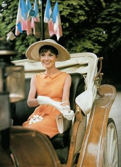 """Audrey Hepburn, in a Givenchy dress, Jean Barthet hat and Gucci handbag, photographed by Bob Willoughby in Paris (France), during the filming of """"Paris - When It Sizzles"""", in August 1962."""