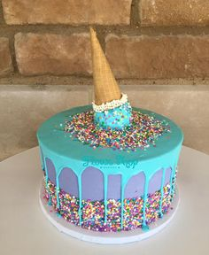 Purple and turquoise drip cake with lots of rainbow sprinkles and an ice cream cone. Love it. @flourshoptx