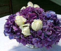 Crisp white roses punctuate an arrangement of purple hydrangeas.