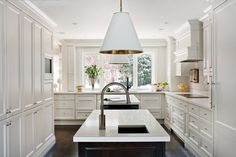 Thomas O'Brien lighting anchors the double islands with the soft brass metal interior of the pendants A larger window now creates a beautiful termination point  Kitchen  Transitional by Elizabeth Metcalfe Interiors & Design Inc