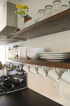 une astuce pour ranger facilement les tasses et les mugs dans une petite cuisine. Utiliser des crochets à vis pour les suspendre à une étagère ouverte !