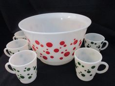 Vintage 1950s Hazel Atlas punch bowl with red polka dot and 5 cups with green polka dots. Although the bowl does not have the Hazel Atlas mark it is definitely by Hazel Atlas. All 5 cups have the HA mark. The bowl has a few dark swirls on the bottom, but look they were made during production, but otherwise in very good used condition with no cracks chips or discoloration. One cup has a dot that shows slight wear. They are in very good used condition with no cracks, chips or discoloration…