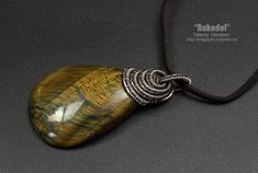 Pendant of natural stone Falcon eye Pendant: 64 x 32 mm A very beautiful large cabochon made from a natural Falcon eye 47 x 32 mm. The nickel silver wire used was 0.8 and 0.3 mm. To give the product a vintage appearance, the wire is patinated (aged) and polished. In the complete set with a