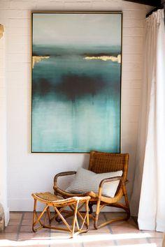 Un rincón para desconectar. Butaca de mimbre, cojín, pintura marina, luz natural tamizada...
