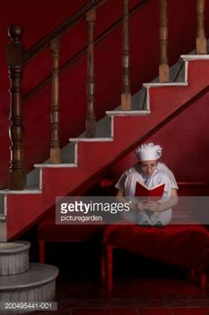 Stock Photo : Female chef reading book beneath stairs