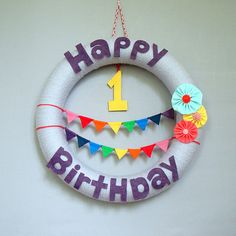 Birthday Yarn Wreath for child's birthday party. Rainbow bunting, fabric flowers, and felt lettering. Modern party decor.