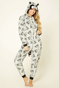 A plush knit PJ jumpsuit featuring an allover raccoon print, hood with embroidered raccoon and ears sticking out, raccoon tail, zippered front, contrast ribbed trim, and long sleeves.