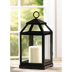 """Candleholders & Candles Home Locomotion Squared glass-paned lantern gets geometric appeal from a simple silhouette and classic matte-black finish. Safely houses a stately pillar candle for hours of enchanting light! Loop at top for hanging; can also stand freely on table or shelf. Metal and glass. 5 1/2"""" x 5 3/4"""" x 12"""" high."""
