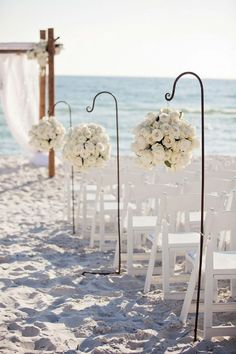 beach wedding in white, i love the floral balls as aisle arrangements leading to the backdrop for the ceremony.