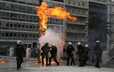 Athens. February 4, 2016. Riot police react to petrol bombs thrown by masked youths in Syntagma Square during a 24-hour general strike against planned pension reforms