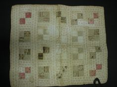 Small cotton doll quilt. Circa 1880-1900. Blocks of 4 -one inch squares joined by rectangular strips. Red, rose, pink and brown squares. White with pink and red pattern used between each square and as a backing.  All hand stitched. Cotton flannel lining.  Documented by MassQuilts on October 24, 2011. #chathamhistoricalsociety, #chatham, #quilt, #antiquequilt, #atwoodhouse, #capecod