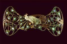 Ouro, esmalte, opalas, diamantes. Este peitoral é constituído por um enorme pavão, articulado, em ouro esmaltado em tons de azul e verde simulando as penas da ave que são ponteadas aqui e ali por pequenas opalas em cabochão, de formato ovalado. O movimento sinuoso das penas da cauda que se enrolam em torno do corpo do pavão, virado sobre a esquerda, é enriquecido por uma equilibrada composição de diamantes, de diversas dimensões, que arrematam a peça de ambos os lados.