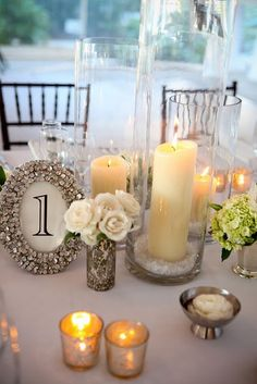 here's an idea - we could mix and match candles with little bunches of the newspaper flowers. It looks pretty in all white. pretty table number frame