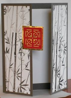 Gate-fold card with bamboo on the doors and a red and gold medallion...