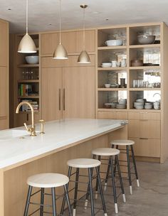Gold hardware and a gold faucet pop next to light wood cabinets and white counters.