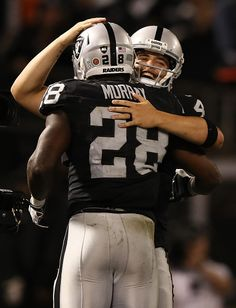 Derek Carr of the Oakland Raiders and Latavius Murray celebrate after a touchdown during the fourth quarter against the Denver Broncos at...