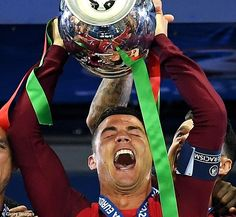 The 31-year-old holds Portugal's first European trophy aloft as he celebrates the extra-time win with his side