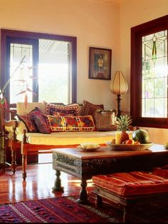ethnic-indian-living-room-interiors Ornately carved coffee table, low ?rattan chairs, polished wooden floor with a tribal rug.