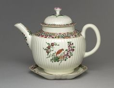 1765 1982,0202.1 Teapot  moulded, shaped , painted in colours with border of flowers; 'parrot' pattern: red bird and flowering branches in centre; gilt rim and enrichment. Date1765 (circa)