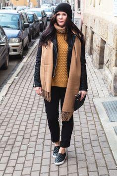 Kleidermädchen trägt ein lässiges Outfit mit Lederjacke, gelben Pullover, schwarzer Stoffhose und beigen Schal von Topshop, Cos,H&M und Mango.