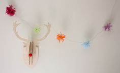 Christmas Craft-Starburst Pom Pom Garland using raffia. i love to buy plain natural raffia and paint it myself with a paintbrush in colours of my choice. my trick is also to add strokes of gold or silver with a permanent marker after i paint it.