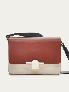 Tricoloured crossbody bag made of caprine and bovine leather with a metal hardware. It features two main compartments, a central zipped pocket, a foldover flap with magnetic clasp fastening, an adjustable shoulder strap and lining.