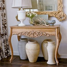 An ornately-carved console paired with rustic urns is a cool combination (design by Tim Clarke).