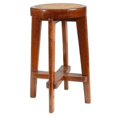 PIERRE JEANNERET Caned Teak Bar Stool from Chandigarh, India  (Swiss, 1896-1967)  Crafted of solid teak with a round caned seat supported on four tapered legs joined by an X-stretcher. $8500