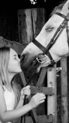 Horse and girl kiss. They both have the same sweet expression on their faces!