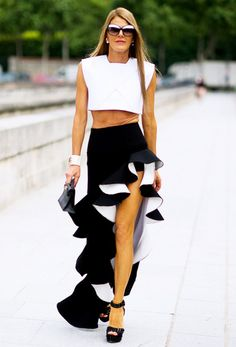 Anna Dello Russo wears a white crop top, maxi ruffle skirt, and platform sandals