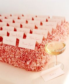 Tented Seating Cards:  Tented seating cards are elevated to new heights atop a pillow of carnations. Cut several standard bricks of floral foam in half horizontally, soak in water, and place in shallow plastic flower-box trays. Snip off the carnation heads, leaving a little bit of stem on each, and insert into the foam; each half-brick should hold about two dozen carnations and four seating cards.  xo,   Paramount Wedding Designs & Event Planning. Serving CT, NY, MASS, RI