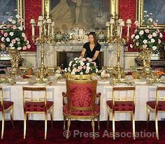 A Royal Collection curator from the Royal Collection puts the final touches to the Coronation State Banquet display at Buckingham Palace, as part of an exhibition in the State Rooms at Buckingham Palace.