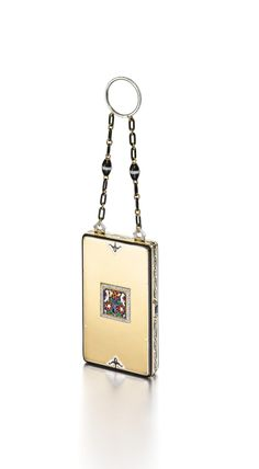 Vanity case composed of polished gold with white and black enamel trim, the central square motif depicting two birds within a floral scene applied with enamel, framed by a diamond border, the sides applied with black enamel in the form of meandering vines, with diamond and enamel thumbpiece, suspended from a black enamel, diamond and gold chain supported by a diamond-set ring; interior fitted with a mirror, powder compartment, and two lipstick sections, one with detachable lipstick holder