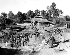 Burmese with incense in foreground watch column of WWII soldiers march through village. Photographer Unknown