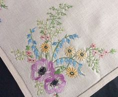 """A beautiful vintage linen hand embroidered tray cloth or table centre piece. Crisp, smooth, quality linen cloth with a double edge and a hand sewn ladderwork detail. Lovely hand embroidery on this cloth ~ neat, raised, compact work using gorgeous coloured threads to form wonderful floral displays in each corner, with a larger display in one corner, which includes anemones. So pretty. In superb, freshly laundered, crisp, starched condition and measures 18"""" x 12 1/2""""   eBay!"""