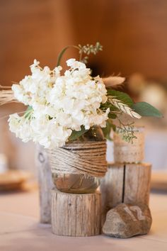 White hydrangeas were placed in jars wrapped with sisal twine. Photo by Wren Photography