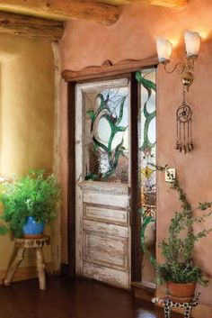 entryway to straw bale home; a stained-glass window in rich colors complements the distressed salvaged door