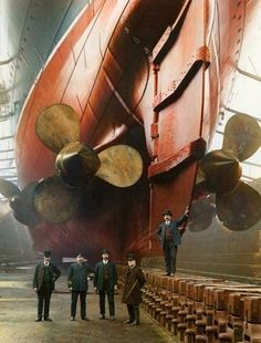Men posing underneath Titanic, near the rudders (colorized)