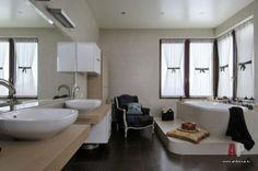 Дизайн интерьера двухэтажной квартиры в новостройке | Просторное помещение хозяйского санузла позволило автору проекта поднять ванну на подиум, расположив ее у окна, и создать в помещении элегантную атмосферу благодаря светлым оттенкам мебели для ванной комнаты Antonio Lupi