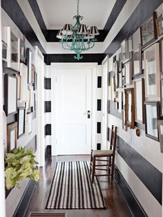 Black and white stripes on the entryway walls, with a runner to match