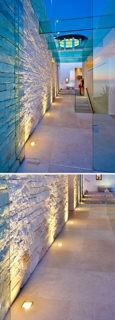 7 Interiors That Use Dramatic Uplighting To Brighten A Space // Warm lights run along the bottom of the entryway wall and highlight the texture of the stones used in the wall.