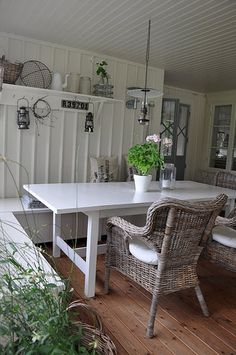 Loving the gray wicker chairs and a clean-lined white table.