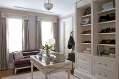 Lilac & gray office/walk in closet design with plum velvet sofa, metallic lilac damask wallpaper, lilac ikat pillows, gray cornice box with gray silk curtains window panels, white built-ins and white gold desk.
