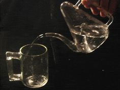 Pyramid Teapot pouring into a Cup of Tantalus - cadagan teapot - no lid, fill it halfway and you can't spill
